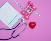 Stethoscope and a calendar. Doctor`s appointment and service in the hospital. Dumbbell and measure tape on pink background. royalty free stock images