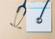 Stethoscope and a calendar. Doctor`s appointment and service in the hospital. royalty free stock photography