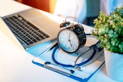 Stethoscope, clipboard, clock and laptop on doctor desk. Blue stethoscope, clipboard, pen, table clock and laptop computer on doctor desk. Blurred white doctor royalty free stock image