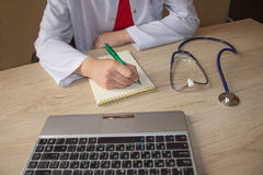 Stethoscope with clipboard and Laptop on desk. Medicine doctor`s working table Royalty Free Stock Image