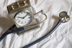 Stethoscope and Clock. A stethoscope and clock lay on a lab coat royalty free stock image