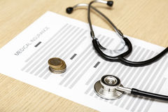 Stethoscope and coins laying on the blank of medical insurance. Stock Images