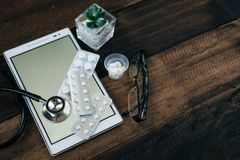 Stethoscope, digital tablet and medicine on wooden table background stock images