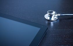 Stethoscope on digital tablet pc on wood table Royalty Free Stock Images