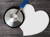 Stethoscope for doctor and medical nursing people in hospital, healing of patients. Wooden background and paper heart. Stethoscope for doctor and medical stock photos