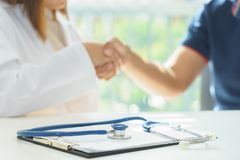 Stethoscope on doctor and patient are shaking hands, medical diagnosis concept royalty free stock photos