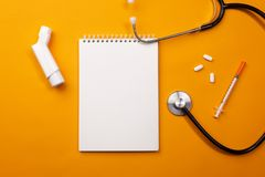 Stethoscope in doctors desk with notebook, inhaler and pills, top view stock photos