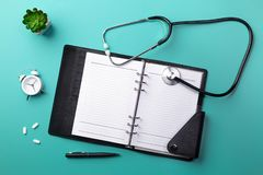 Stethoscope in doctors desk with notebook, keyboard, mouse, glasses, syringe, ampoules, inhaler and pills. Top view with place for your text stock photos