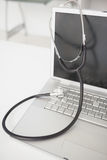 Stethoscope draped over silver laptop Royalty Free Stock Photo