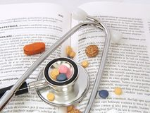Stethoscope & Drugs on medical book Royalty Free Stock Photos