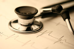 Stethoscope and EKG. Close-up of stethoscope and a waveform from an EKG test as a background stock photo