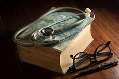 Stethoscope with eyeglasses,pen and antique book. Royalty Free Stock Photography