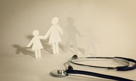 Stethoscope and the family paper doll.the concept of health. Photo with copy space Royalty Free Stock Image