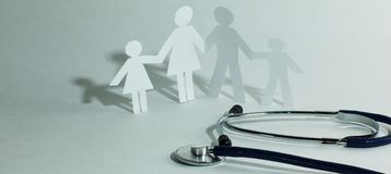 Stethoscope and the family paper doll.the concept of health. Photo with copy space Stock Image