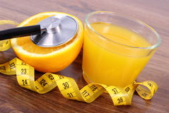 Stethoscope, fresh orange, juice and tape measure, healthy lifestyles and nutrition Royalty Free Stock Photo