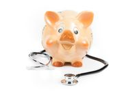 Stethoscope in front of piggy bank a piggy bank, concept for save money. Stethoscope in front of a piggy bank on white background with space for text, concept Stock Photo