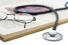 Stethoscope and glasses on a book Stock Photography