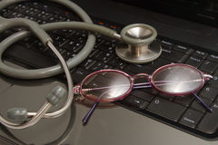Stethoscope and glasses rest on  notebooks Stock Image