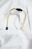 Stethoscope in a gown pocket. A blue-gold stethoscope in a white gown pocket Royalty Free Stock Images