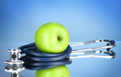 Stethoscope and green apple Stock Images