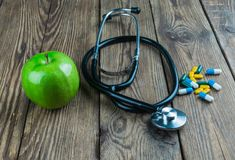 Stethoscope and green apple on a wooden background stock photography