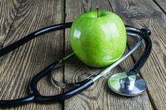 Stethoscope and green apple on a wooden background stock photo