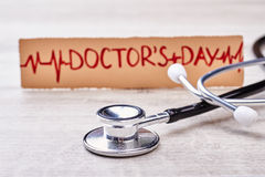 Stethoscope and greeting for doctor. Paper card on wooden backdrop. Congratulations for cardiologist Stock Photos