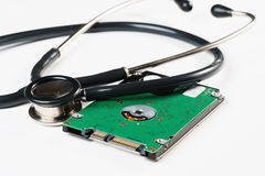 Stethoscope and hard disk drive on white background Stock Photos