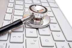 Stethoscope head on computer keyboard Stock Photo