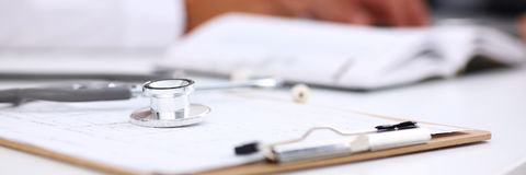 Stethoscope head lying on medical forms closeup Stock Photos