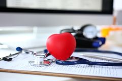 Stethoscope head and red heart shape toy lying on medical application form. At worktable in doctor office. Cardio therapeutist cardiac physical exam arrhythmia stock photos