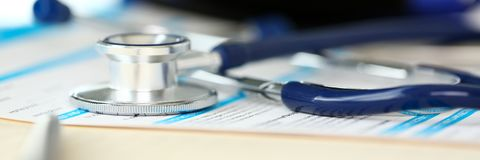 Stethoscope head and silver pen lying on medical application form. At worktable in doctor office closeup stock image