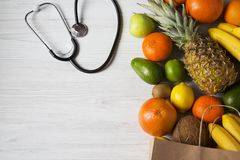 Stethoscope health diet. Paper bag of different fruits on white wooden background. Flat lay. Top view. Copy space stock photography