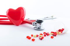 Stethoscope, heart and pills lying on the table Royalty Free Stock Image
