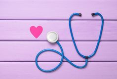 Stethoscope and heart on a purple wooden table. Cardiology equipment for diagnosing cardiovascular diseases. Top view. Flat lay Stock Photo