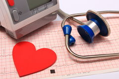 Stethoscope, heart shape, blood pressure monitor on electrocardiogram Stock Images