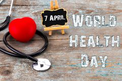 Stethoscope and heart symbol with inscription World Health Day o. N wooden background royalty free stock photography