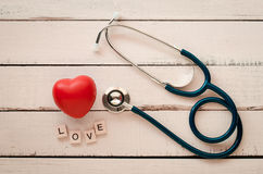 Stethoscope heart and the word `love`on wooden floor. Stock Image