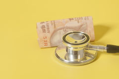 Stethoscope and indian 10 rupee notes on yellow Stock Photos
