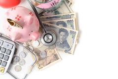 Stethoscope on Japaness yen banknote and piggy bank royalty free stock photography
