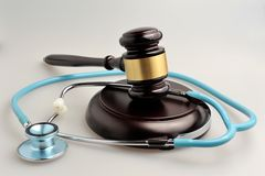 Stethoscope with judge gavel on gray Stock Images