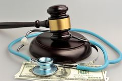 Stethoscope with judge gavel, money on gray background Royalty Free Stock Photography