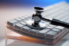 Stethoscope on keyboard. Stethoscope on white keyboard lit by blue and orange lights stock images