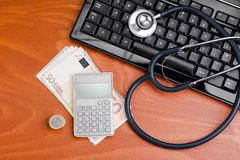 Stethoscope on a keyboard with a calculator Stock Photography