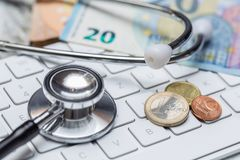 Stethoscope and keyboard with coins and money concept Stock Photo