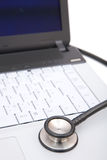Stethoscope on laptop Stock Images