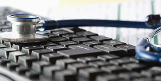 Stethoscope on a laptop computer and document Stock Photography