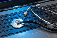 Stethoscope on laptop keyboard Royalty Free Stock Images