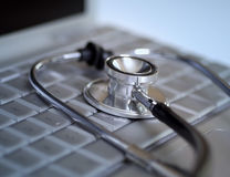 Stethoscope laying on computer Stock Image