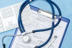 Stethoscope laying over doctors emergency report Royalty Free Stock Images